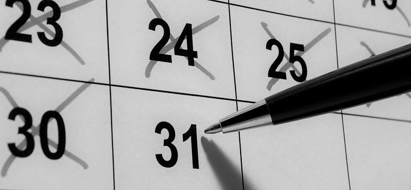 close up photo of a pen about to cross off the 31st on a calendar