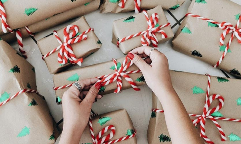 hands tying the bow of a present