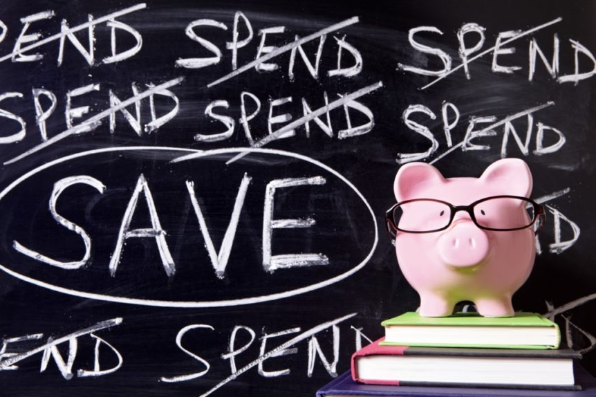 Piggy Bank in front of a chalk board with 'spend' crossed out and 'save' circled