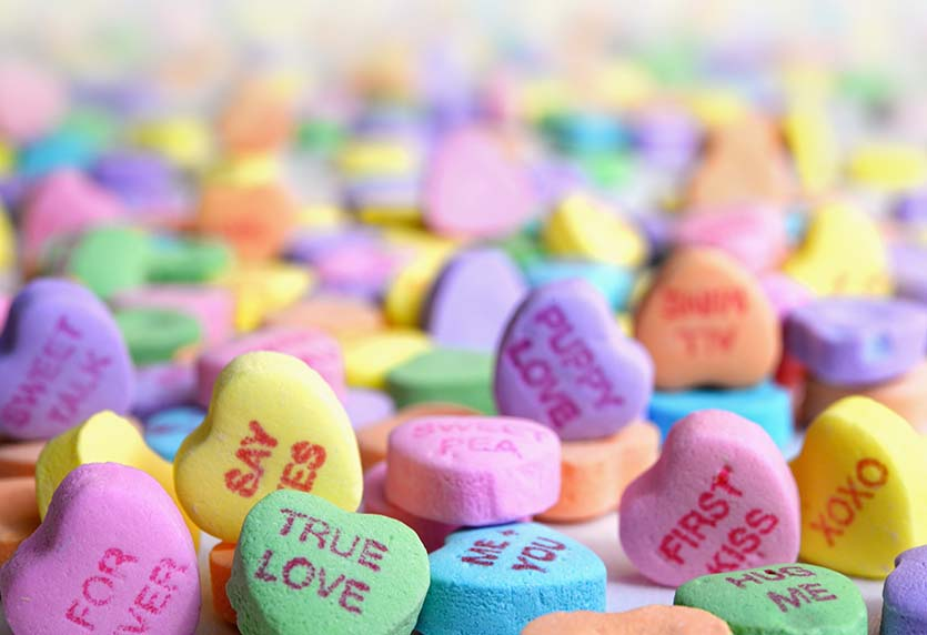 close up photo of candy conversation hearts in multiple pastel colors